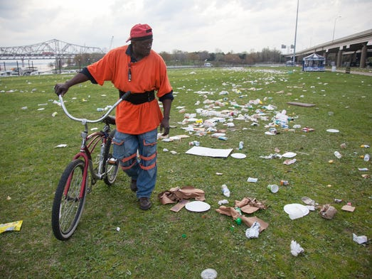 Rickey Taylor walks past trash on the Great Lawn at Waterfront Park after Thunder Over Louisville. April 13, 2013