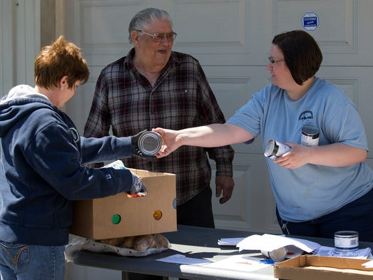 Christian Appalachian Project case workers Sherri Barnett, left, and Candace Riddell, right, assist Oliver Miller in packing his monthly commodity box, Thursday, April 10, 2014 at Grateful Bread Food Pantry in Mt. Vernon. Photo by Jonathan Palmer, Special to the CJ  This day focuses on the elderly that are in need and about 120 come and receive groceries and other provisions donated or purchased from God's Pantry in Lexington.