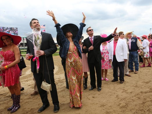 Cancer patient Jill Conley, third from left, and husband Bart, second from left, walk in the Kentucky Oaks Survivors Parade at Churchill Downs ahead of the race in Louisville. May 2, 2014.