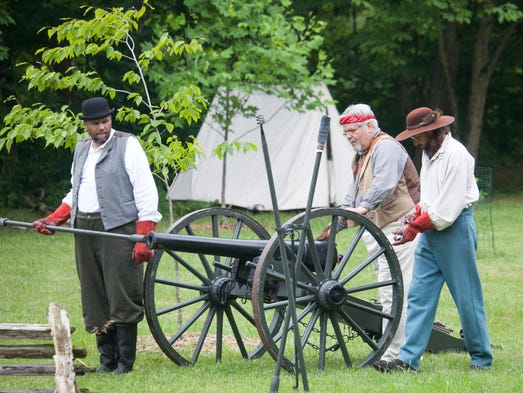 Mikal Moore, left, Dennis Jorgensen, and Todd Biehle prepare the cannon to fire during an artillery demo.  June 8, 2014