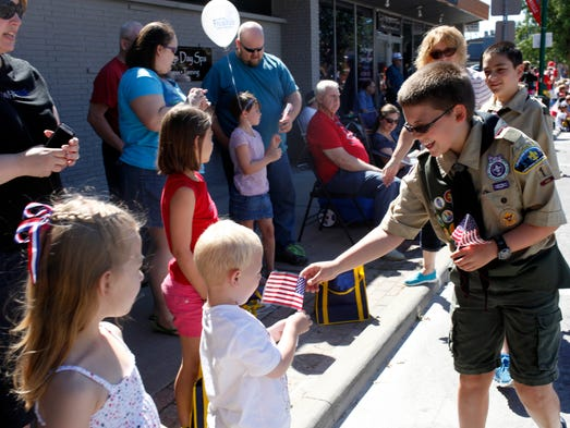Boy Scout Alex Cox, 13, right, passes out American flags while walking in the Celebrating Freedom Parade held in Historic Downtown Jeffersonville on July 4th. The parade is held every year to celebrate America's birthday with an emphasis on honoring veterans of past and current wars. July 4, 2014