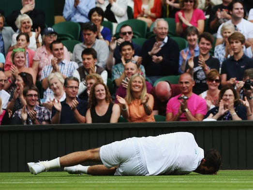 Radek Stepanek  lies on the court after slipping during his match against Novak Djokovic.