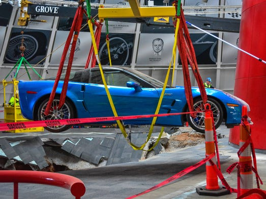 """Workers use a crane to recover the first Chevrolet Corvette, the 2009 Corvette ZR-1 """"Blue Devil,"""" from the sinkhole at the National Corvette Museum"""