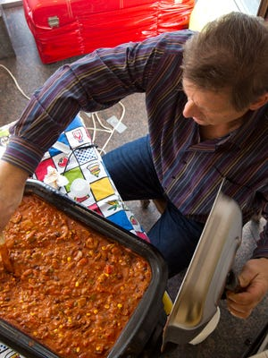 Roger Steiner, co-owner of Bangles and Bags, stirs chili during Chili Fest in 2016.