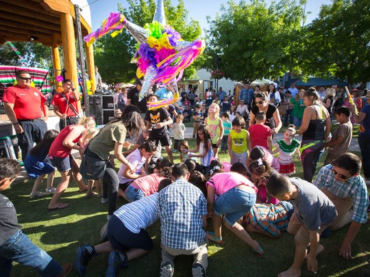 Children scramble to pick up candy from a piñata at Mesilla Plaza during the Cinco de Mayo fiesta, May 7, 2016.