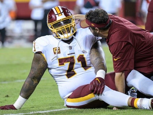"This Oct. 2, 2017 photo shows Washington Redskins offensive tackle Trent Williams (71) being treated during the first half of an NFL football game in Kansas City, Mo. Williams has played through so many injuries that he figures ""something has to be torn or broken"" to not be in uniform. After missing just three games for injury from 2012-2016, Williams has missed three of the past five with so severe a problem in his right knee that it'll require surgery at some point. (AP Photo/Reed Hoffmann)"
