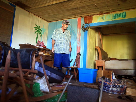Howard Hoffmann surveys his damaged home after Hurricane