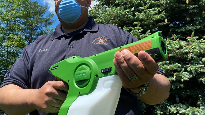 Paramedic Dominic Singh, chief of operations at the Spencer Rescue Squad, holds an electrostatic sprayer donated to the town's emergency services departments by Laurie Letendre of A. Arsenault & Sons, a local landscaping company.