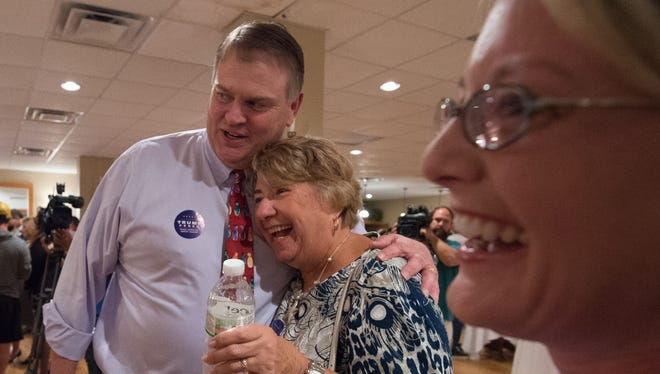 Colin Bonini, left hugs Carole Andrejko of Long Neck while attending a Republican party gathering at Frazier's in Dover to see the results of the primary election.