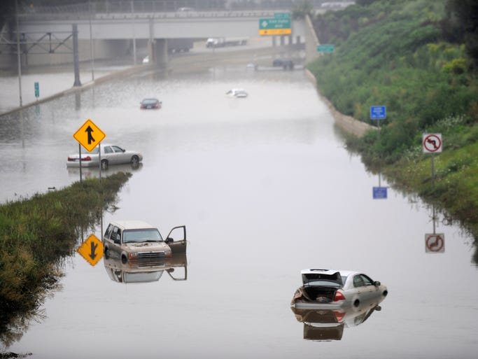 Cars stranded in flooded expressway.