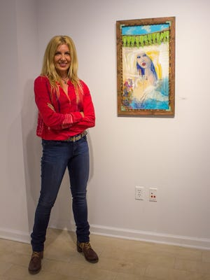 "Amy Jarvis poses next to her painting ""Words Left Unsaid,"" which recently won Viewer's Choice at a membership art show hosted by the Thelma Sadoff Center for the Arts."