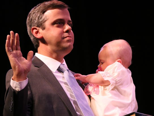 Toby Barker is sworn in as the 35th mayor of Hattiesburg while holding his daughter, Audra, during the inauguration ceremony June 29 at the Saenger Theater. Barker and other newly elected municipal leaders were part of a major change that swept through some local city governments.