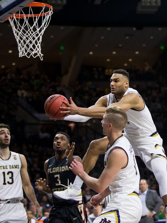 Notre Dame's Austin Torres, right, grabs a rebound over teammates Nikola Djogo (13) and Rex Pflueger and Florida State's Trent Forrest (3) during the first half of an NCAA college basketball game Saturday, Feb. 10, 2018, in South Bend, Ind. (AP Photo/Robert Franklin)