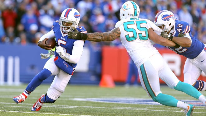 Bills quarterback Tyrod Taylor is brought down by Miami's Koa Misi (55).  Taylor rushed for 44 yards in a 33-17 win.