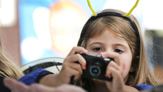 Audrie Blohm of Appleton concentrates on getting a photo of a honeybee during a demonstration last fall at the annual Honey Sunday event at Mosquito Hill Nature Center in New London.