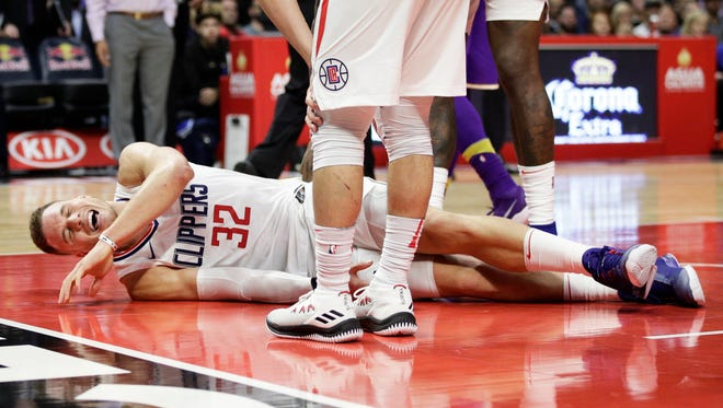 Blake Griffin grimaces in pain after a collision during the second half of a game against the Lakers.