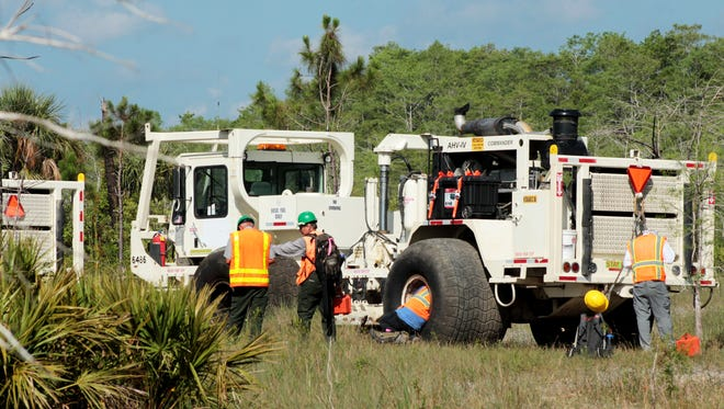 Survey crews work in the Big Cypress National Preserve in 2017 near heavy trucks Texas-based Burnett Oil Co. used to search for oil and gas. The trucks are equipped with vibrating steel plates that are pressed against the ground and send back seismic signals that are analyzed for underground geological formations that may contain oil or gas. Environmental groups had sued to try to stop the work, alleging that the National Park Service did not review the plans carefully enough for potential environmental damage.