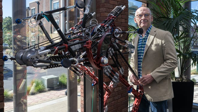Ken Ford stands with a robot he's dubbed the Ostrich.