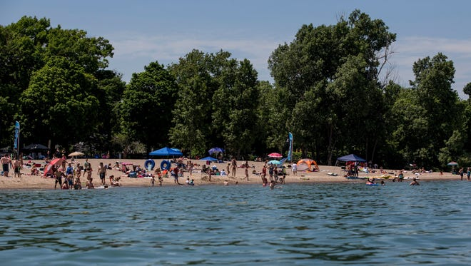 Hundreds of people fill the beach and water Saturday, June 18, 2016, at Lakeside Beach in Port Huron.