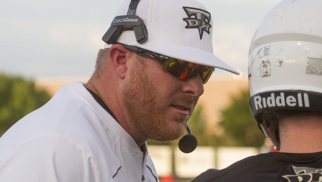 Carl Franke, former Desert Hills football head coach, talks to a player on Aug. 26.