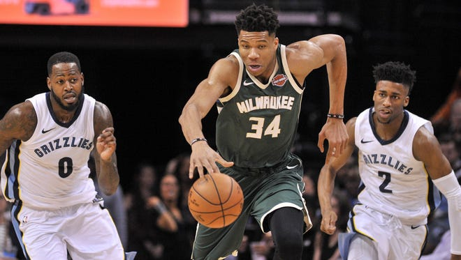 Bucks forward Giannis Antetokounmpo  pushes the ball up court against, leaving a pair of Grizzlies defenders in his wake during the first half Monday.