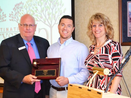 Norris Flowers, left, president of Destination Gettysburg, and Tammy Myers, right, board chairwoman, present Max Felty with a plaque for his year of service as Destination Gettysburg s board chairman over the past year.