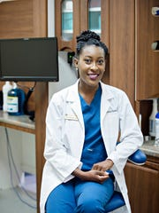 Dr. Dominique Shamburger sits in one of the dental