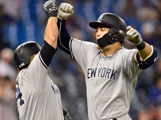 New York Yankees' Giancarlo Stanton, right, celebrates his home run against the Toronto Blue Jays during the 13th inning of a baseball game Wednesday, June 6, 2018, in Toronto.