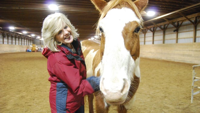 Kimm Eick brushes Lacey during a Just for Women Power Up class at Rattle Run Farms.