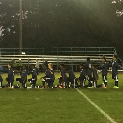 The entire World of Inquiry/School 58 boys soccer team knelt during the national anthem before Tuesday's 1-0 win at Aquinas Institute.