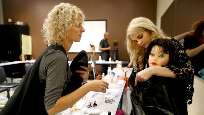 Beth Smith, left, the program director at Georgia Career Institute helps student Sarah Callis put her cape on her mannequin during class Tuesday, Aug. 25, 2015.