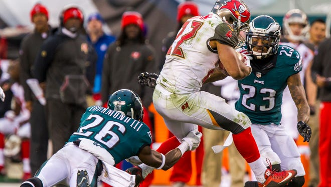 Buccaneers running back Doug Martin cuts between Eagles corners Walter Thurmond III (No. 26) and Nolan Carroll II (No. 23) in the fourth quarter of the Eagles 45-17 loss to the Tampa Bay Buccaneers in Philadelphia on Sunday afternoon.
