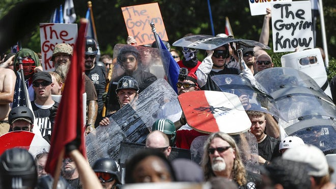 """White nationalist groups march through Emancipation Park in a """"Unite the Right"""" rally Saturday in Charlottesville, Va."""