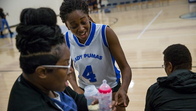 """De'Janae breaks away from a team huddle during a timeout in th game against Indianapolis Lighthouse to explain the correct ratio of water to baby formula for her daughter, Za'Nyla, on Wednesday, Sept. 13, 2017. """"She's a preemie,"""" Dajanae explained. """"It has to be this way. Four ounces of water for this many scoops."""""""