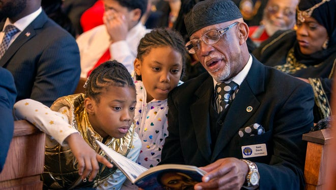 Qeristin Warnick, left, and her sister Makayla look at the program with their grandfather Councilman Sam Davis during the Martin Luther King, Jr. annual commemorative service at Ebenezer Baptist Church in Atlanta.
