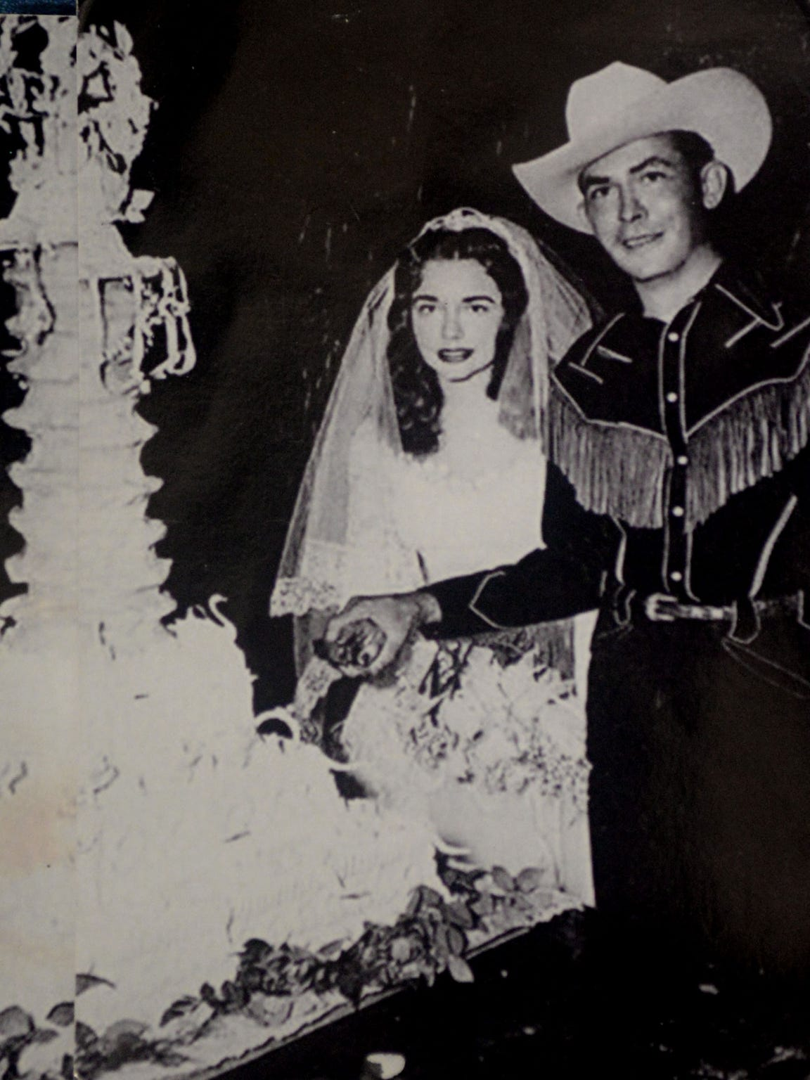 The wedding photo of Hank Williams and Billie Jean Jones with the cake.