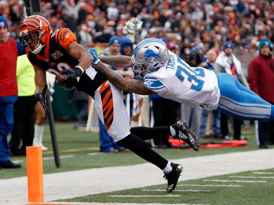 Bengals receiver Tyler Boyd is pushed out of bounds by Lions cornerback Teez Tabor after a 6-yard reception Dec. 24, 2017 in Cincinnati.