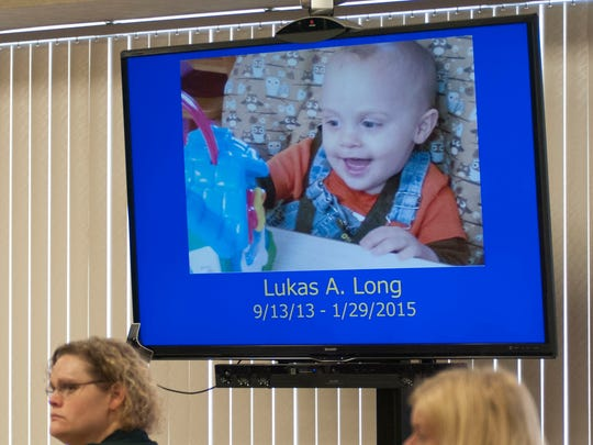 A photo of Lukas Long is displayed on a screen beside his mother, Elizabeth Long, during opening statements Wednesday, Feb. 17, 2016 in Circuit Judge Michael West's courtroom. Elizabeth Long is charged with second-degree murder and second-degree child abuse in 16-month-old Lukas' death.