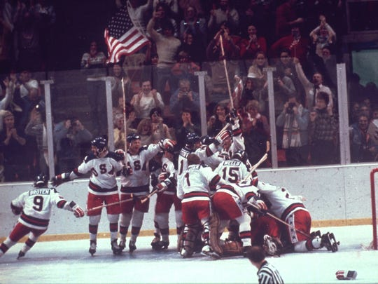 """** FILE ** The U.S. hockey team pounces on goalie Jim Craig after a 4-3 victory against the Soviets in the 1980 Olympics, as a U.S. flag waves from the partisan Lake Placid, N.Y. crowd, Feb. 22, 1980.  The movie """"Miracle,"""" which opens Friday, Feb. 6, 2004,  nationwide, tells the story of 20 fresh-faced college kids who upset the seemingly unstoppable Soviets 4-3 en route to a gold medal at the Olympics in Lake Placid, N.Y. (AP Photo/ file) ORG XMIT: CO502"""
