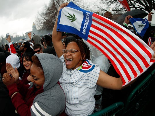Trisha Parker-Madison of Chicago celebrates by waving a flag to promote marijuana legalization during the Mile High 420 Festival, April 20, 2018, in Denver. The annual celebration was projected to attract an estimated 50,000 people in Civic Center Park.