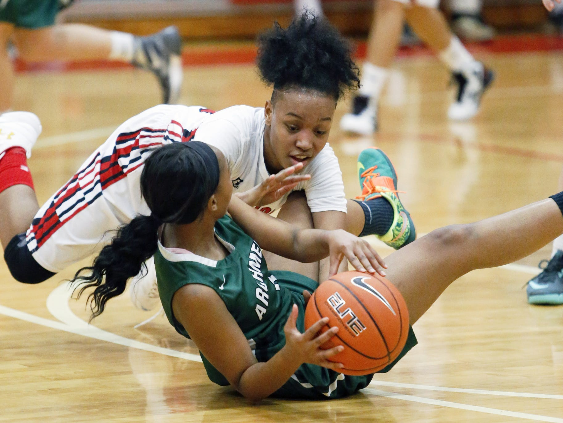 William Penn's Alize Felton falls on Archmere's Danaziah Brown as they scrap over a loose ball in the Auks' 42-39 win at William Penn in the opening round of the DIAA state tournament.