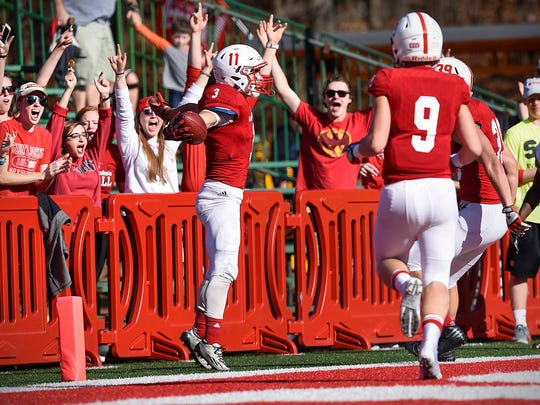 St. John's running back Dusty Krueger, 3, celebrates his touchdown against Hamline with fans and teammates during the first half Saturday, Nov. 5, at Clemens Stadium.