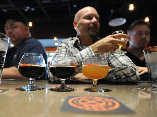 Randy Stanley, a patron of Black Bottle Brewing, samples one of four Black Bottle beers he tried during the brewery's grand opening in 2012.