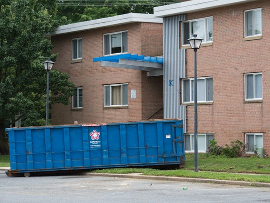 View of a dumpster outside building unit K at Alder Park Apartments in Dover's Caesar Rodney Village.