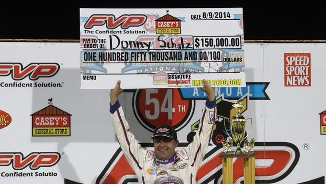 Reese Strickland/For the Register Donny Schatz celebrates with his $150,000 first-place check after winning the 54th Annual Knoxville Nationals early Sunday. Schatz won for the eighth time in nine tries at the event. Aug 9, 2014; Knoxville, IA, USA; Donny Schatz (15 ) celebrates in winners circle after winning the World of Outlaws 54th Annual Knoxville Nationals.  Schatz won his 8th race in 9 tries at the Knoxville Speedway.   Credit: Reese Strickland-For the Register