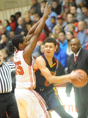 Seton Catholic's Billie Webster looks for an open teammate as Tyrone Washington guards him Monday night.