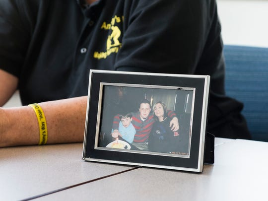 A framed photo shows Gina DeMaria, right, with her son Anthony, center, in early 2014. After Anthony passed away from a heroin overdose, Gina started a nonprofit called Anthony's Way to help those dealing with addiction and their families get connected with the right resources.