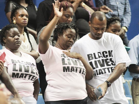 "Attendees wearing ""Black Lives Matter"" T-shirts sing"