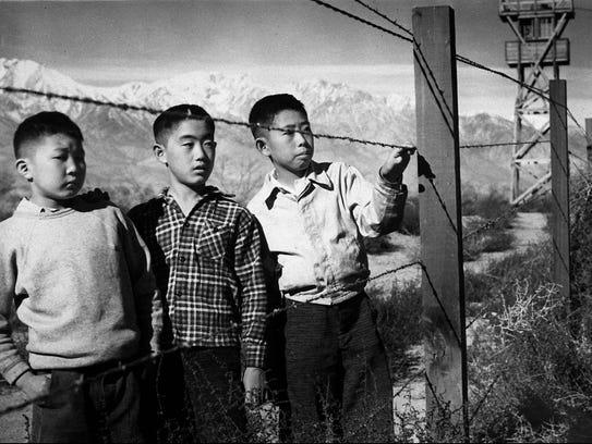 Children stand behind barbed wire at the Manzanar internment