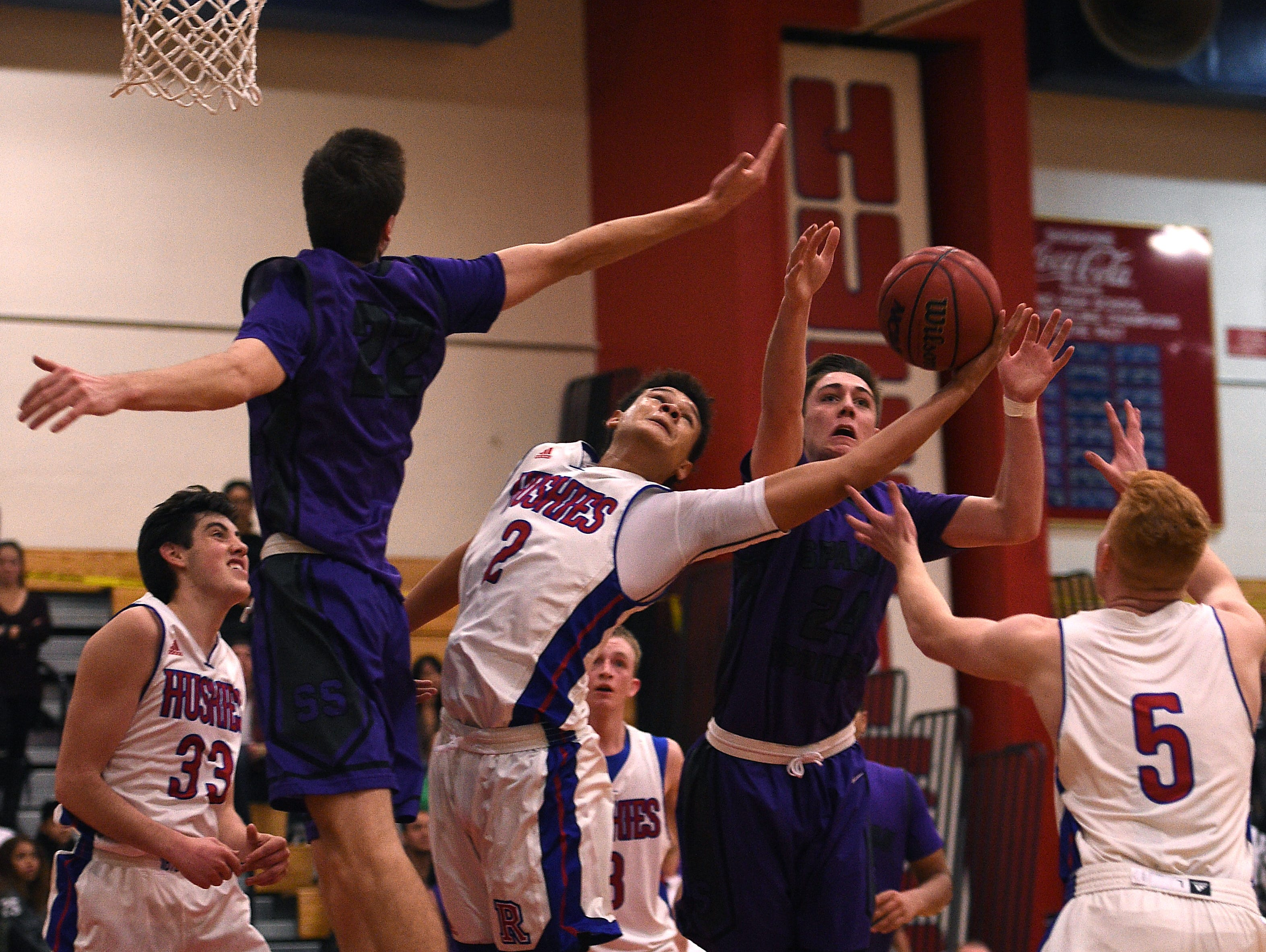 Spanish Springs' Josh Prizina (24) and Reno's Logan Shaw (2) fight for a rebound during their basketball game in Reno on Friday.